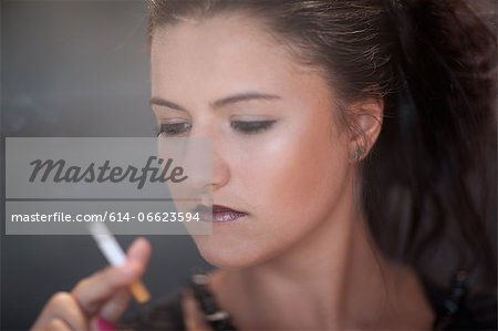 Teenage girl in dark makeup smoking Stock Photo - Premium Royalty-Free, Image code: 614-06623594