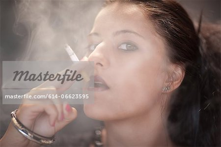 Teenage girl in dark makeup smoking Stock Photo - Premium Royalty-Free, Image code: 614-06623595