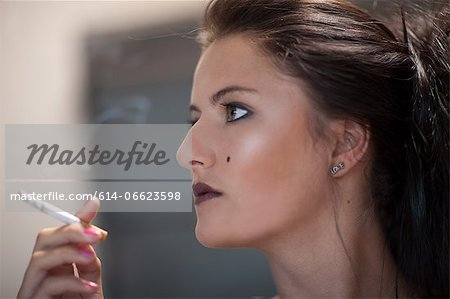 Teenage girl in dark makeup smoking Stock Photo - Premium Royalty-Free, Image code: 614-06623598