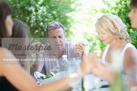 Family saying grace before eating Stock Photo - Premium Royalty-Free, Image code: 614-06623604