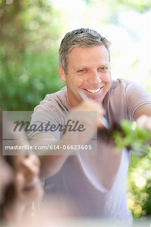 Man serving himself salad at table Stock Photo - Premium Royalty-Free, Image code: 614-06623605
