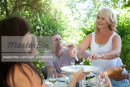 Woman serving salad at table outdoors Stock Photo - Premium Royalty-Free, Image code: 614-06623608