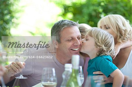 Boy kissing father at table outdoors Stock Photo - Premium Royalty-Free, Image code: 614-06623612