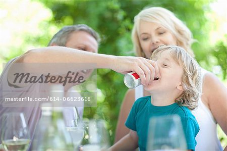 Father giving son soda at table Stock Photo - Premium Royalty-Free, Image code: 614-06623616