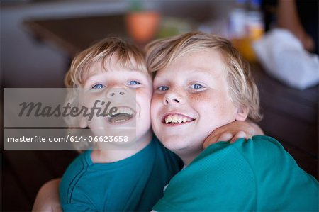 Smiling boys hugging in living room Stock Photo - Premium Royalty-Free, Image code: 614-06623658