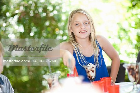 Girl having ice cream sundae at party Stock Photo - Premium Royalty-Free, Image code: 614-06623760