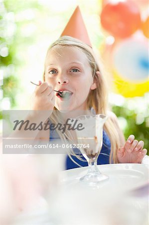 Girl having ice cream sundae at party Stock Photo - Premium Royalty-Free, Image code: 614-06623764