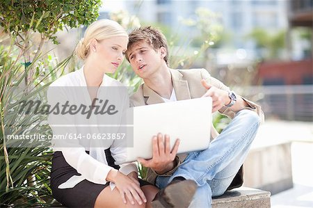 Business people using laptop outdoors Stock Photo - Premium Royalty-Free, Image code: 614-06623857