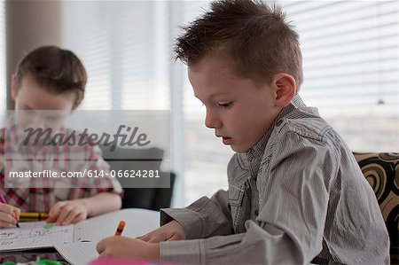 Boys coloring together at table Stock Photo - Premium Royalty-Free, Image code: 614-06624281