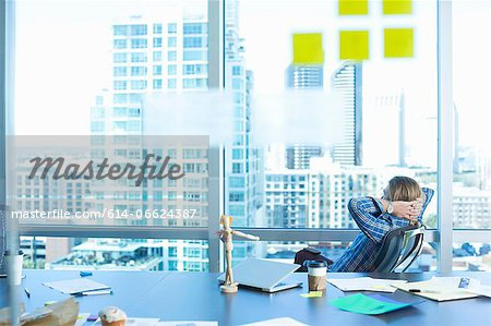 Businessman relaxing at desk in office Stock Photo - Premium Royalty-Free, Image code: 614-06624387