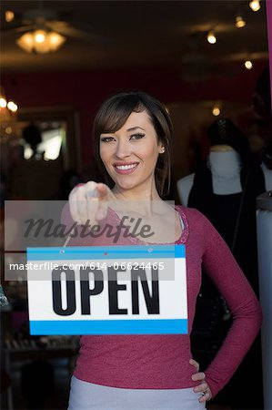 Woman holding open sign in store Stock Photo - Premium Royalty-Free, Image code: 614-06624465