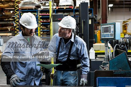 Workers talking in metal plant Stock Photo - Premium Royalty-Free, Image code: 614-06624497