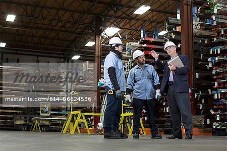 Workers and businessman in metal plant Stock Photo - Premium Royalty-Free, Image code: 614-06624536