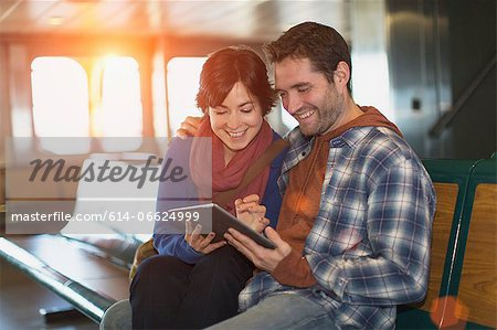 Couple using tablet computer on ferry Stock Photo - Premium Royalty-Free, Image code: 614-06624999