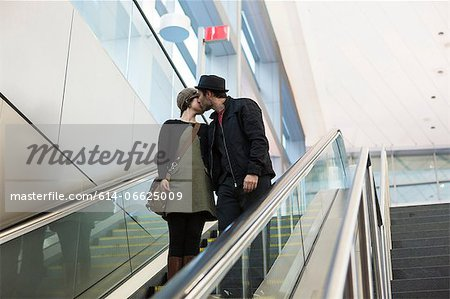 Couple kissing on escalator outdoors Stock Photo - Premium Royalty-Free, Image code: 614-06625009
