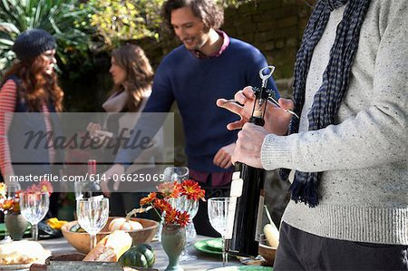 Man uncorking bottle of wine at table Stock Photo - Premium Royalty-Free, Image code: 614-06625069