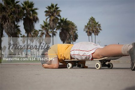 Boy laying on skateboard in park Stock Photo - Premium Royalty-Free, Image code: 614-06625246