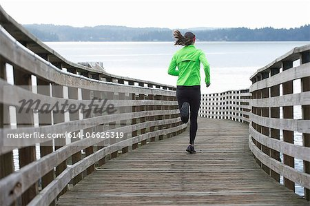 Woman running on wooden dock Stock Photo - Premium Royalty-Free, Image code: 614-06625319
