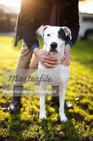 Man holding dog in park Stock Photo - Premium Royalty-Free, Image code: 614-06625424