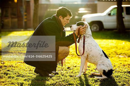Man petting dog in park Stock Photo - Premium Royalty-Free, Image code: 614-06625425