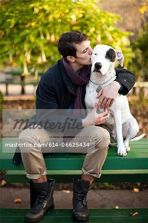 Man petting dog on park bench Stock Photo - Premium Royalty-Free, Image code: 614-06625434