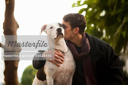 Man kissing dog outdoors Stock Photo - Premium Royalty-Free, Image code: 614-06625436