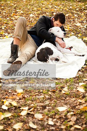 Man and dog relaxing on picnic blanket Stock Photo - Premium Royalty-Free, Image code: 614-06625439