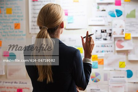 Woman holding pen, rear view Stock Photo - Premium Royalty-Free, Image code: 614-06718082