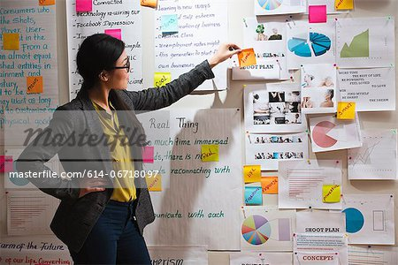 Woman with adhesive notes and papers on wall Stock Photo - Premium Royalty-Free, Image code: 614-06718097