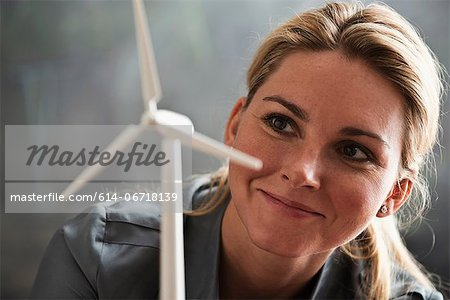 Woman with model wind turbine Stock Photo - Premium Royalty-Free, Image code: 614-06718139