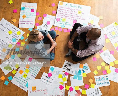 Colleagues sitting cross legged on floor with papers and adhesive notes Stock Photo - Premium Royalty-Free, Image code: 614-06718144