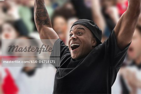 Man at sports game with arms raised Stock Photo - Premium Royalty-Free, Image code: 614-06718171