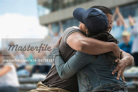 Couple hugging at sports game Stock Photo - Premium Royalty-Free, Image code: 614-06718187