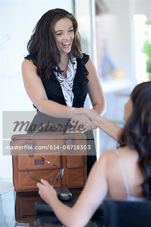 Businesswomen shaking hands in office Stock Photo - Premium Royalty-Free, Image code: 614-06718303