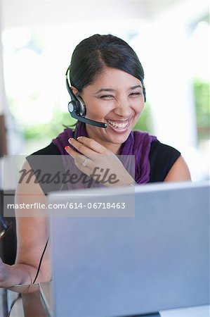 Businesswoman wearing headset at desk Stock Photo - Premium Royalty-Free, Image code: 614-06718463