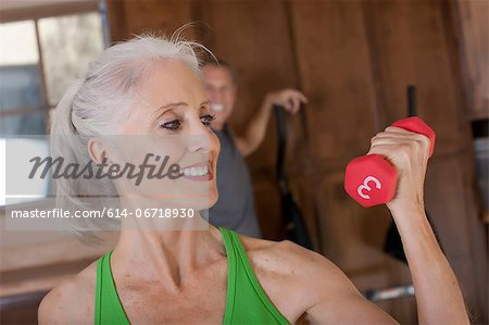 Older woman lifting weights at home Stock Photo - Premium Royalty-Free, Image code: 614-06718930