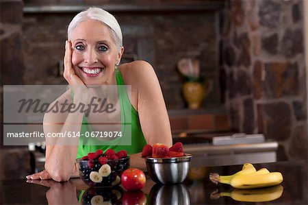 Older woman having fruit in kitchen Stock Photo - Premium Royalty-Free, Image code: 614-06719074
