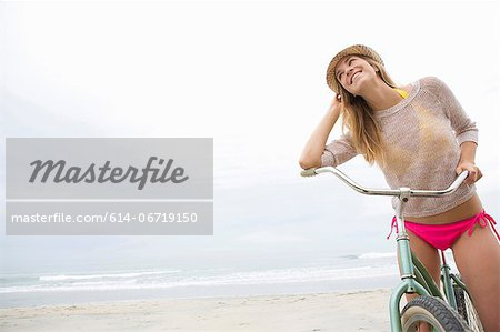 Woman on bicycle on beach Stock Photo - Premium Royalty-Free, Image code: 614-06719150