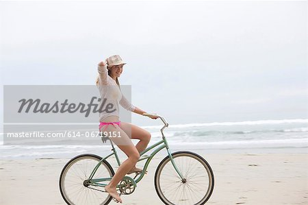 Woman riding bicycle on beach Stock Photo - Premium Royalty-Free, Image code: 614-06719151