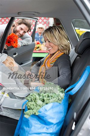 Woman buckling son in car seat Stock Photo - Premium Royalty-Free, Image code: 614-06719261