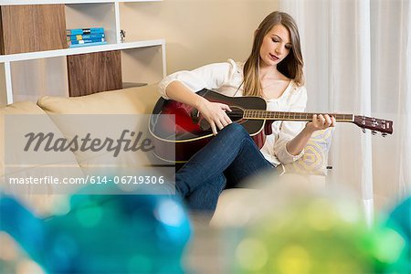Woman playing guitar on sofa Stock Photo - Premium Royalty-Free, Image code: 614-06719306