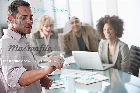 Businessman drawing graph in meeting Stock Photo - Premium Royalty-Free, Image code: 614-06719406