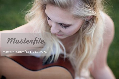 Woman playing guitar in grass Stock Photo - Premium Royalty-Free, Image code: 614-06719773