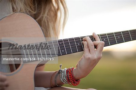 Woman playing guitar in grass Stock Photo - Premium Royalty-Free, Image code: 614-06719789