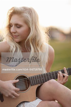 Woman playing guitar in grass Stock Photo - Premium Royalty-Free, Image code: 614-06719795
