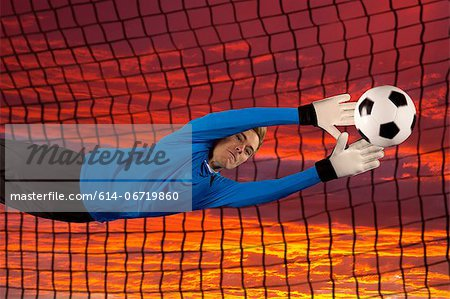 Soccer player deflecting ball in air Stock Photo - Premium Royalty-Free, Image code: 614-06719860