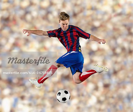 Soccer player kicking ball in air Stock Photo - Premium Royalty-Free, Image code: 614-06719873
