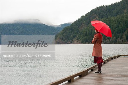 Woman with umbrella on wooden pier Stock Photo - Premium Royalty-Free, Image code: 614-06719895