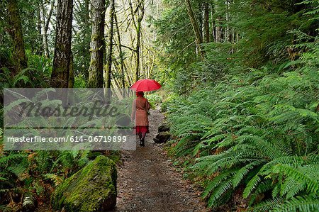 Woman with umbrella walking in forest Stock Photo - Premium Royalty-Free, Image code: 614-06719899