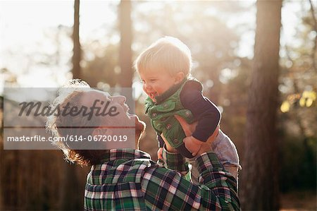 Father carrying son in park Stock Photo - Premium Royalty-Free, Image code: 614-06720019